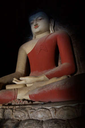 witness: Buddha in red ochre robe, in Bhumiparsa Mudra position, Calling the Earth To Witness the Truth, Dhammayangyi Temple, Bagan,  Myanmar (Burma)