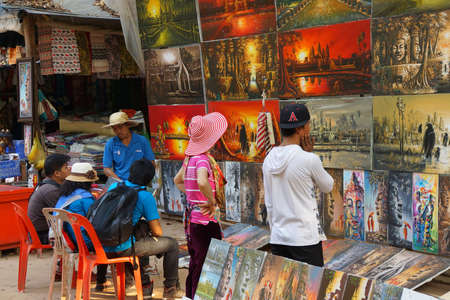 SIEM REAP, CAMBODIA - FEB 14, 2015 - Tourists shop for paintings of Angkor Wat,   Cambodia