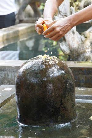 puja: Brahmin priest offers puja at large shiva lingam,  Phnom Kulen, Cambodia