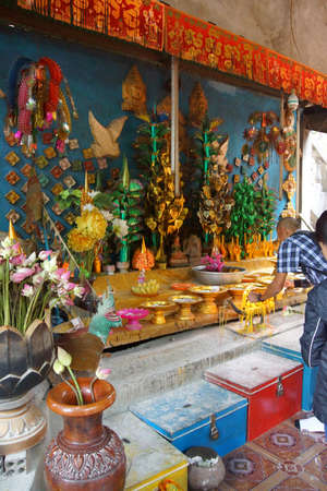 worshipper: PHNOM KULEN, CAMBODIA - FEB 15, 2015 - Worshippers leave offerings at altar of the reclining Buddha,  Phnom Kulen, Cambodia