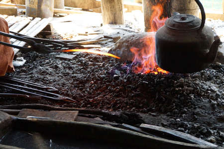 Heating iron in a charcoal fire, to make a knife,  Inle Lake,  Myanmar (Burma) Stock Photo
