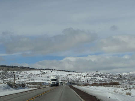 winter road: Trucks on winter highway with snowy hills in southern Utah