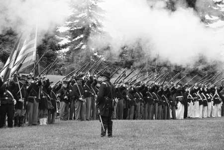 PORT GAMBLE, WA - JUN 20: Civil War reenactors participate in a mock battle. Union infantry line firing a volley.