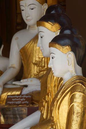 witness: Buddha statues in Bhumiparsa Mudra position, Calling the Earth To Witness the Truth, Shwedagon Pagoda Yangon (Rangoon),  Myanmar (Burma) Stock Photo