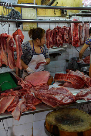 SAIGON - FEB 5, 2015 - Woman chopping meat for sale at the Ben Thanh Market in Saigon (Ho Chi Minh City),  Vietnam Editorial