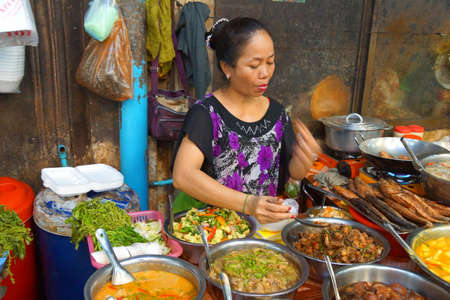 siem: SIEM REAP, CAMBODIA - FEB 16, 2015 - Woman cooking lunch in the market of  Siem Reap,  Cambodia Editorial