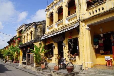 yellow ochre: HOI AN, VIETNAM - FEB 3, 2015 - Traditional yellow ochre building with palm trees, Hoi An, Vietnam