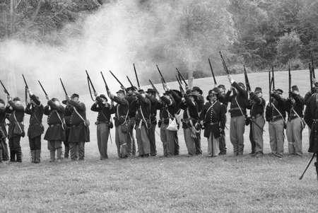 PORT GAMBLE, WA - JUN 20: Civil War reenactors participate in a mock battle. Union infantry line firing a volley.