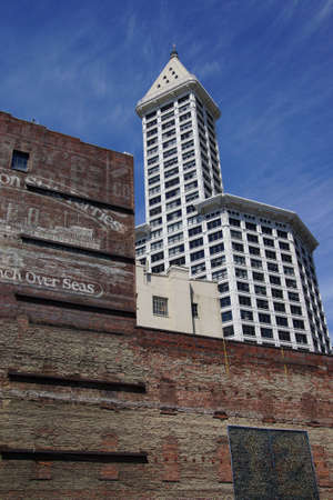 pioneer: SEATTLE - JUL 23, 2015 - The Smith Tower rises above old brick building near Pioneer SquareSeattle, Washington