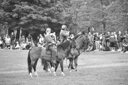reenactor: PORT GAMBLE, WA - JUN 20: Civil War reenactors participate in a mock battle. Union and Confederate cavalry maneuvering in open field.