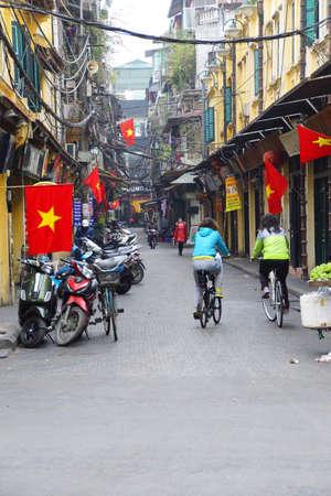 HANOI, VIETNAM - FEB 1, 2015 - Bicycles on narrow street, with red Vietnamese flag,  Hanoi,  Vietnam Editorial