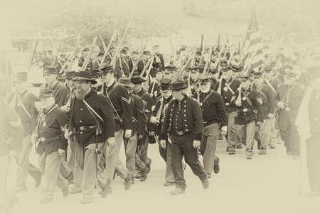reenactor: PORT GAMBLE, WA - JUN 20: Civil War reenactors participate in a mock battle. Union army marching to battle in column formation. Editorial