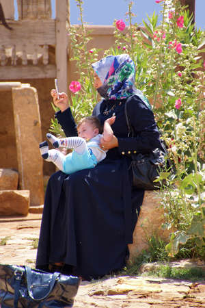 fidgety: URFA, TURKEY - JUN 8, 2014 - Young Turkish mother tries to use cell phone with fidgety baby,  in Southeastern Turkey