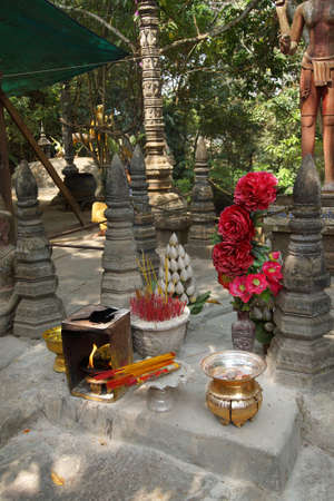 Incense and other offerings at a shrine at  Phnom Kulen, Cambodia