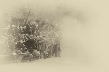 reenactor: PORT GAMBLE, WA - JUN 20: Civil War reenactors participate in a mock battle. Union infantry line firing a volley.