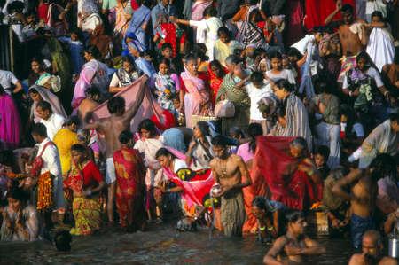 benares: VARANASI, INDIA - NOV 16, 1976 - Hindu pilgrims bathe in the Ganges River at dawn, Varanasi ( Benares), India Editorial