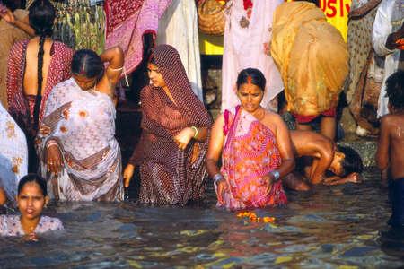 varanasi: VARANASI, INDIA - NOV 16, 1976 - Hindu pilgrims bathe in the Ganges River at dawn, Varanasi ( Benares), India Editorial