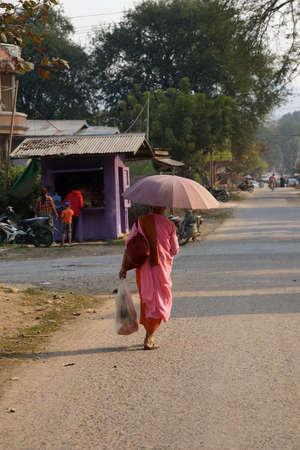 dhamma: Buddhist nun in pink robes with umbrella Hsipaw,  Myanmar (Burma)