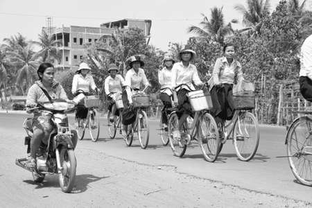 thom: KAMPONG THOM, CAMBODIA - FEB 12, 2015 - Students bicycle home from school along a busy highway,  near Kampong Thom,  Cambodia