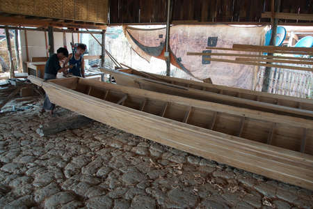 work boat: INLE LAKE, MYANMAR - MAR 1, 2015 - Boat builders work in their shop on  Inle Lake,  Myanmar (Burma)