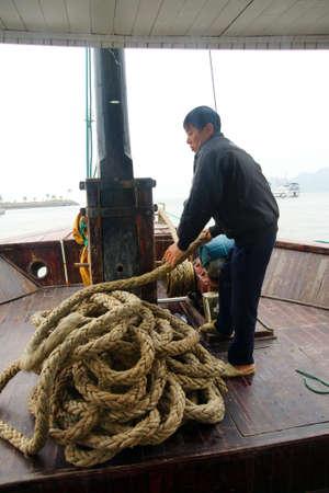 halong: HALONG BAY, VIETNAM - FEB 2, 2015 - Crewman hauling in the anchor on cruise ship junk,  Halong Bay, Vietnam Editorial