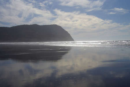 oregon coast: Afternoon sun dramatically breaks through clouds behind Tilamook Head, with reflections on beach, Seaside, Oregon coast