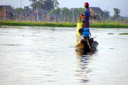 Leg rowing fisherman works his nets on  Inle Lake,  Myanmar (Burma)