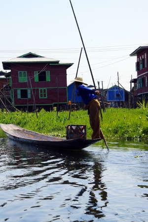 Been roeien visser stuwt zijn kleine boot op Inle Lake, Myanmar (Birma)
