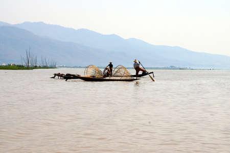 脚ローイング漁師は、インレー湖で, ミャンマー (ビルマ) の彼の小さいボートを推進します。
