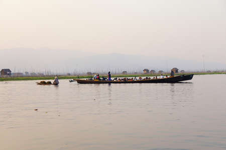 ferries: INLE LAKE, MYANMAR - FEB 28, 2015 - Large oared boat ferries local villagers across  Inle Lake,  Myanmar (Burma)