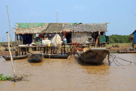 Fishing nets hang out to dry on huts of the Kompong Kleang floating fishing village,  Cambodia