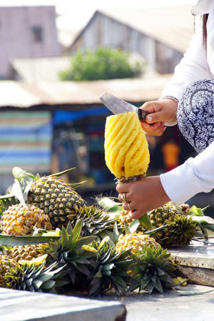 cai rang: Vietnamese woman prepares pineapple for eating,  at the Cai Rang floating market on the Mekong River,  Vietnam