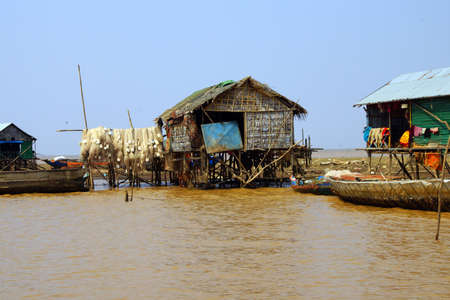 hang out: Fishing nets hang out to dry on huts of the Kompong Kleang floating fishing village,  Cambodia
