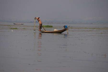 インレー湖で, ミャンマー - 2015 年 2 月 28 日 - 脚ローイング漁師は、インレー湖で, ミャンマー (ビルマ) の彼の網を設定します 写真素材 - 47761684