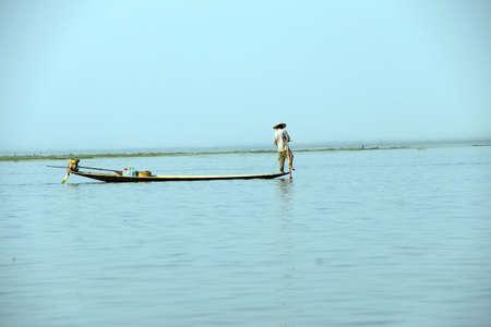 インレー湖で, ミャンマー - 2015 年 2 月 28 日 - 脚ローイング漁師は、インレー湖で, ミャンマー (ビルマ) の彼の網を設定します