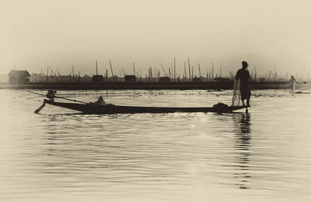 Been roeien visser werkt zijn netten op Inle Lake, Myanmar (Birma)