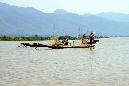 脚ローイング漁師は、インレー湖で, ミャンマー (ビルマ) の彼の小さいボートを推進します。 写真素材 - 47744269