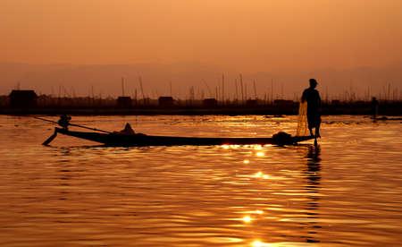 脚ローイング漁師は、インレー湖で, ミャンマー (ビルマ) の彼の網