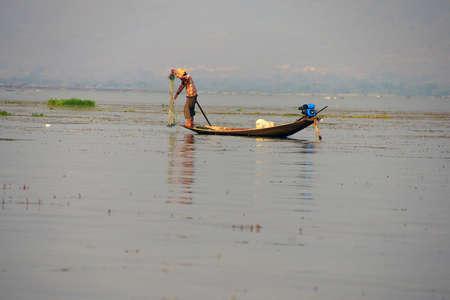 インレー湖で, ミャンマー - 2015 年 2 月 28 日 - 脚ローイング漁師は、インレー湖で, ミャンマー (ビルマ) の彼の網を設定します 写真素材 - 47762043