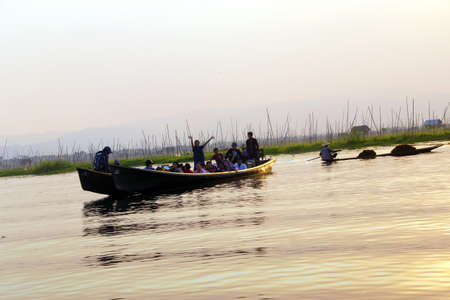 inle: INLE LAKE, MYANMAR - FEB 28, 2015 - Large oared boat ferries local villagers across  Inle Lake,  Myanmar (Burma)