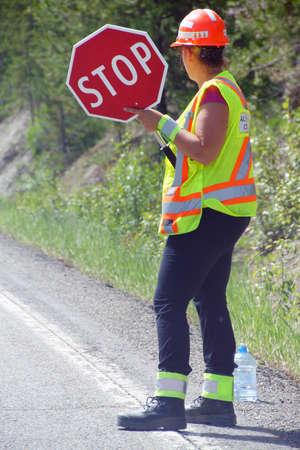 一時停止の標識、ブリティッシュ ・ コロンビア、カナダを持って建設クルー flagger 写真素材