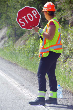 construction crew: Construction crew flagger holding stop sign,   British Columbia, Canada