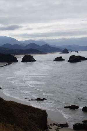 onshore: Sea stacks and misty mountains with weather front moving onshore near Cannon Beach,   Oregon Coast