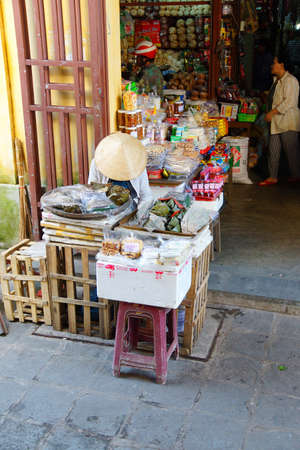 hoi an: HOI AN, VIETNAM - FEB 3, 2015 - Woman selling vegetables and fruit at the central market of  Hoi An, Vietnam