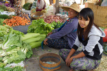 weekly market: INLE LAKE, MYANMAR - MAR 1, 2015 - Young woman selling fresh vegetables at the weekly market on  Inle Lake,  Myanmar (Burma)