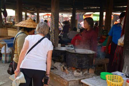 weekly market: INLE LAKE, MYANMAR - MAR 1, 2015 - Young woman selling freshly cooked food at the weekly market on  Inle Lake,  Myanmar (Burma)
