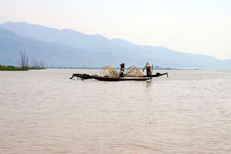 脚ローイング漁師は、インレー湖で, ミャンマー (ビルマ) の彼の小さいボートを推進します。 写真素材 - 47973705