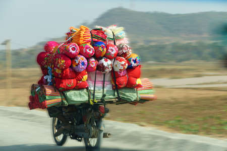 Carrying quilts and bedding on back of motorcycle, Skoun,  Cambodia Reklamní fotografie