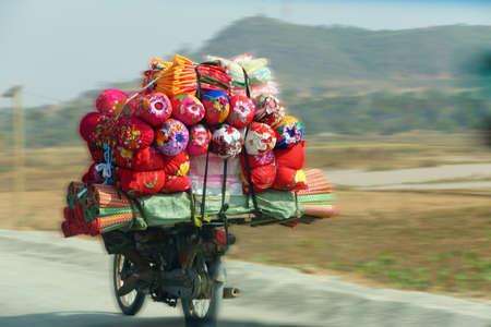 Het dragen van quilts en beddengoed op de achterkant van de motorfiets, Skoun, Cambodja