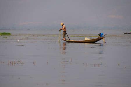 Inle Lake, MYANMAR - 28 februari 2015 - Leg roeien visser zet zijn netten op Inle Lake, Myanmar (Birma) Redactioneel